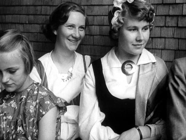 Ein Mädchen und zwei junge Frauen lächeln in die Kamera, 1950er-Jahre.