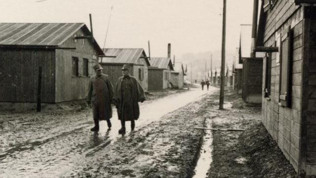 Zwei Soldaten auf einem Weg zwischen den Baracken.