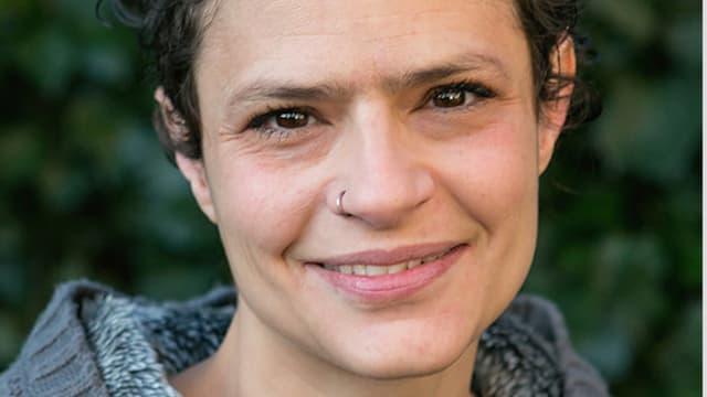 Eine Frau mit dunklen, kurzen Haaren, braunen Augen und Nasenring-Schmuck blickt in die Kamera und lächelt.