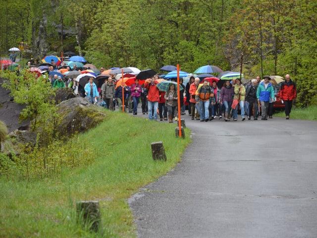 Eine grosse Gruppe Menschen in farbiger Regenkleidung wandert durchs Tal. Zuvorderst ein Kruzifix.