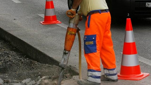 Ein Bauarbeiter in orangen Hosen und einem Presslufthammer hämmert auf eine Strasse ein.