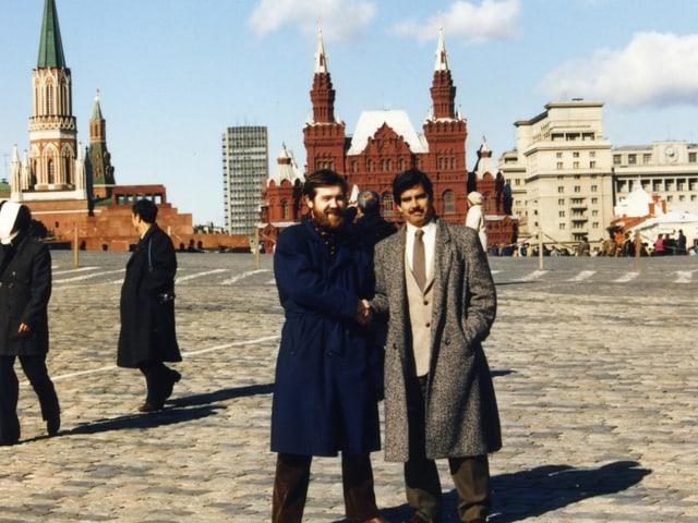 Zwei Männer stehen vor dem Kreml in Moskau und schütteln sich die Hand.