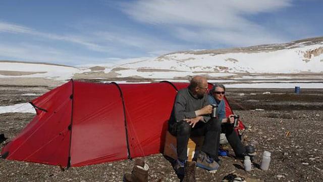 Björn Klauer und Regina Elpers sitzen vor einem roten Zelt.