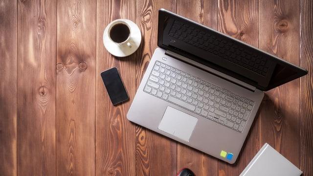Notebook auf einem Holztisch, daneben steht eine  Tasse Kaffee.