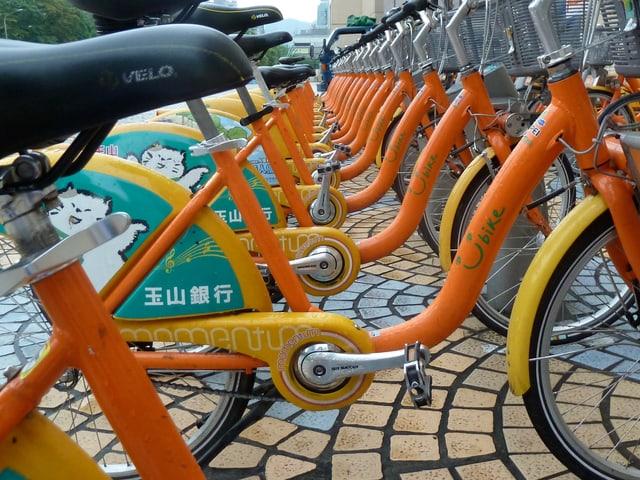 Blick durch die Rahmen hindurch auf eine Reihe abgestellter Youbike-Velos.
