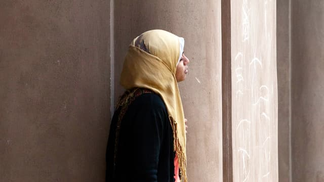 Eine Frau mit Hidschab steht vor einer Moschee.