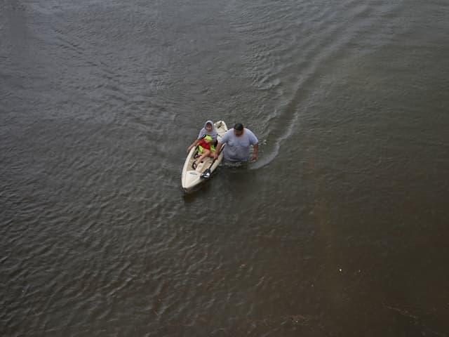 Ein Mann schiebt eine im Kajak sitzende Frau durch das Wasser.