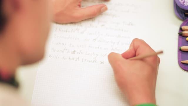 Erwachsene Person schreibt an einem Kurs für Illettristen Sätze auf einen Zettel.