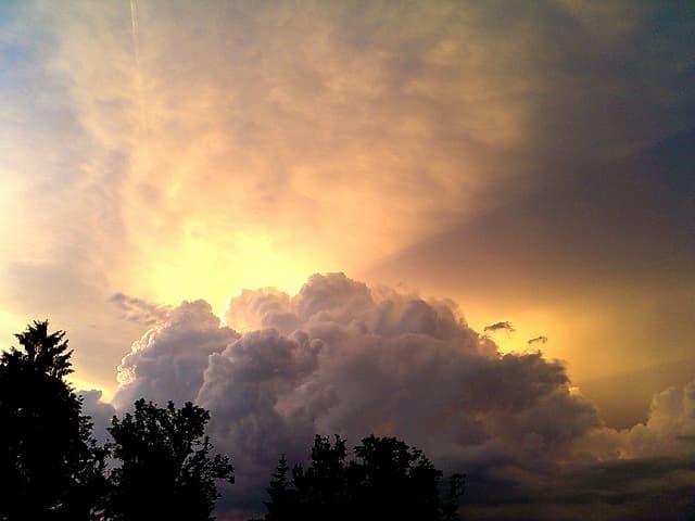 Eine Gewitterwolke bäumt sich auf, dahinter Sonnenstrahlen