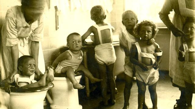 Aufnahme aus ca. 1930 mit Krippenkinder beim Zähneputzen und auf dem Hafen sitzen.