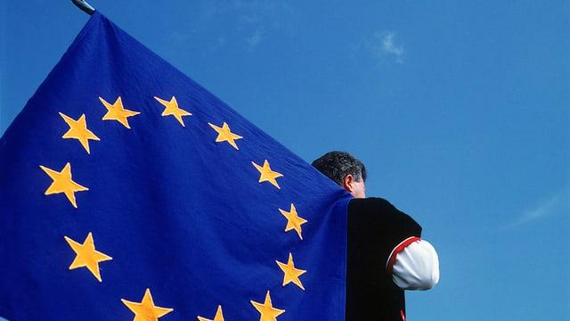 Schweizer Älpler mit geschulterter Europafahne.