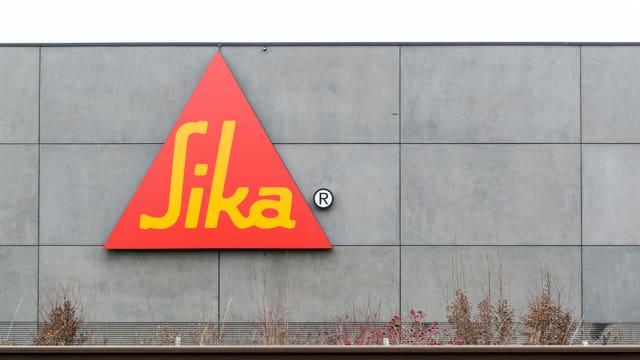 Purtret dal logo da la Sika, ch'è in triangul cotschen cun scrittira melna.