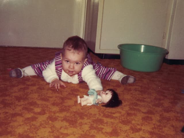 Mädchen mit Puppe auf Boden.