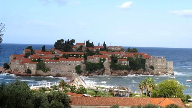 Die Adira-Insel Sveti Stefan umgeben vom Meer und unter blauem Himmel.