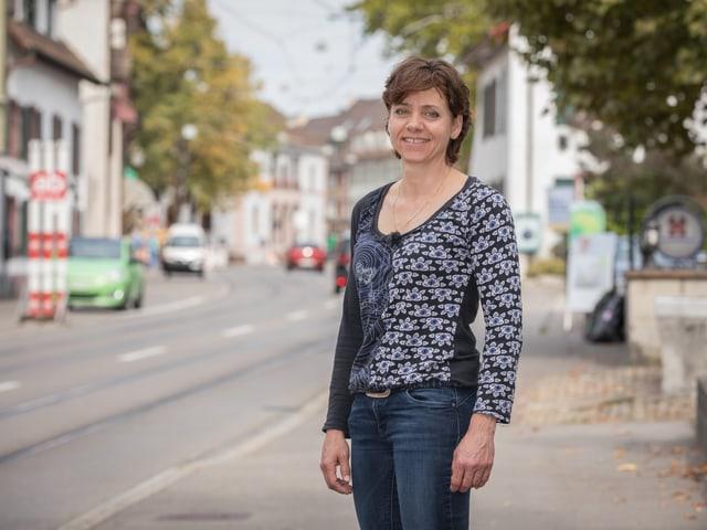 Eien Frau steht auf einer befahrenen Strasse in Riehen und lächelt in die Kamera.