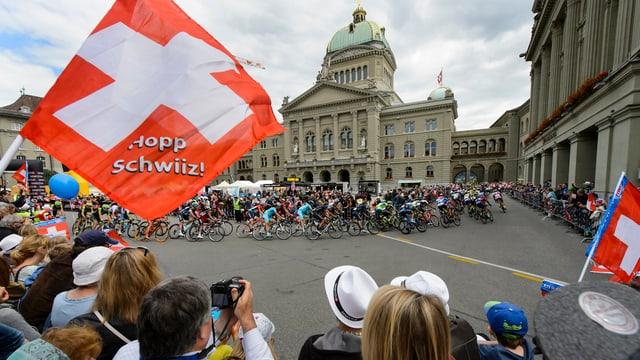 Aspectaturs dal Tour de Suisse e davos la gruppa dals velocipedists avant la Chasa federala.