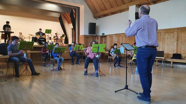 Musicants e musicantas giuvnas cun lur dirigent.