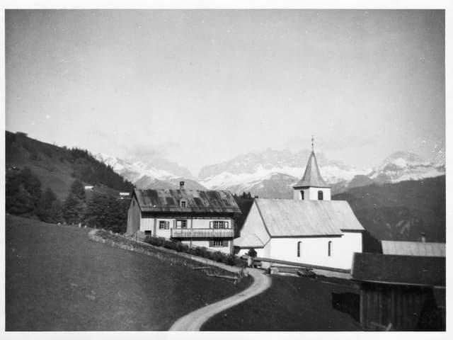 Schwarzweiss-Fotografie einer Kirche. Gleichdaneben ein Pfarrhaus.