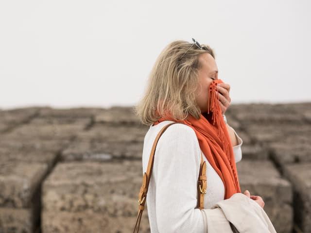 Eine Frau steht vor den Fäkalkunst-Blöcken und hält sich mit dem Schal die Nase zu