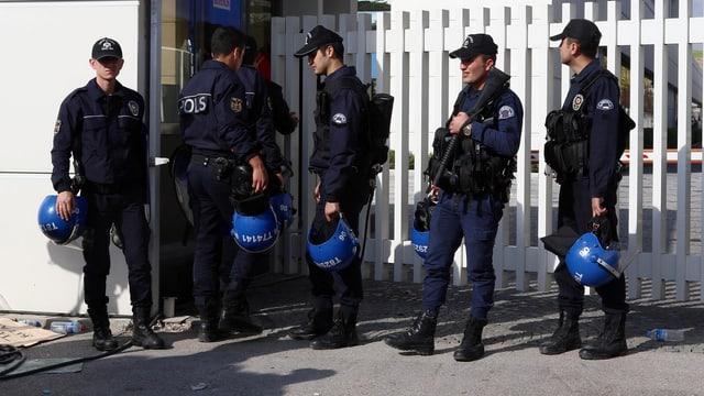 Mehrere Polizisten stehen vor einem Gebäude.