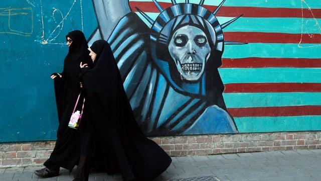 Frauen im Tschador in Teheran, dahinter die Freiheitsstatue als Skelett.
