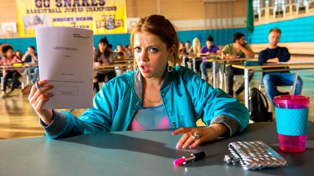 """Ein stark geschminktes Mädchen sitzt in einer Turnhalle an einem Tisch. Um sie herum sitzen andere Schüler an Einzeltischen. Das Mädchen schaut verständnislos drein und hält einen Stapel Papiere mit der Aufschrift """"Leistungstest"""" in die Höhe."""