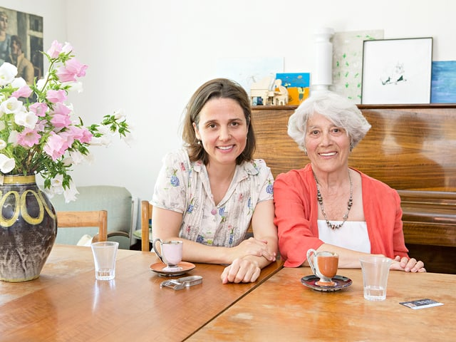 Dagny Gioulami und Areti Guioulami an einem Tisch. Auf dem Tisch sind Tassen.