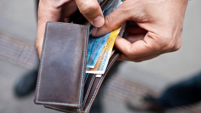 Hand mit offener brauner Geldbörse.