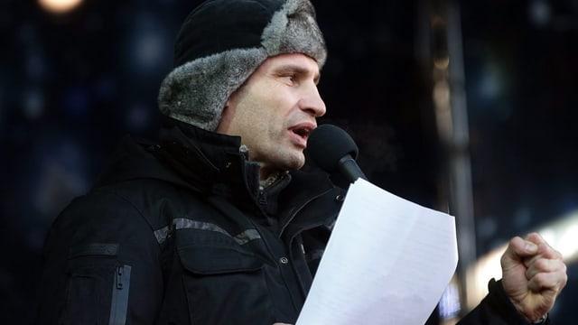 Klitschko mit Fellmütze und einem Manuskript bei seiner Rede.