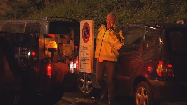 Ein Lastwagen will rückwärts auf einen Parkplatz fahren. Doch ein Auto steht im Weg. Ein Chauffeur steht dazwischen und funkt.