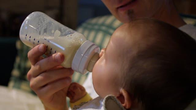 Ein Mann gibt einem Kleinkind die Flasche