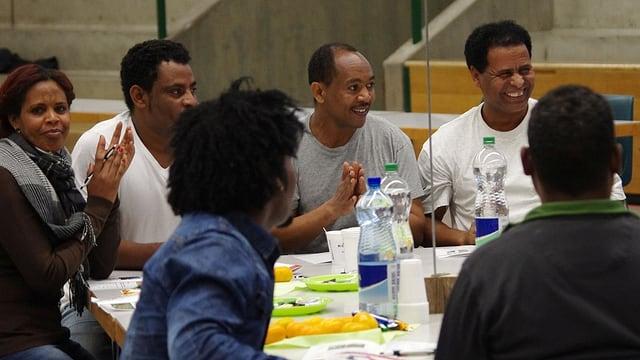 Sechs dunkelhäutige Menschen debattieren lebhaft an einem Tisch