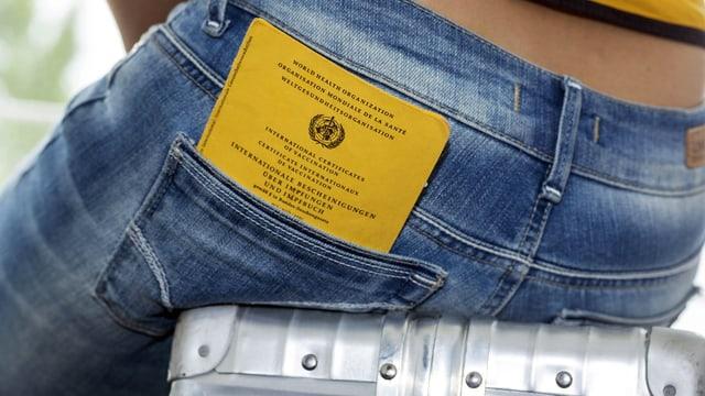 Hinteransicht einer Person, die auf einem Alukoffer sitzt und den Impfausweis nachlässig in der Gesässtasche ihrer Jeans eingesteckt hat.
