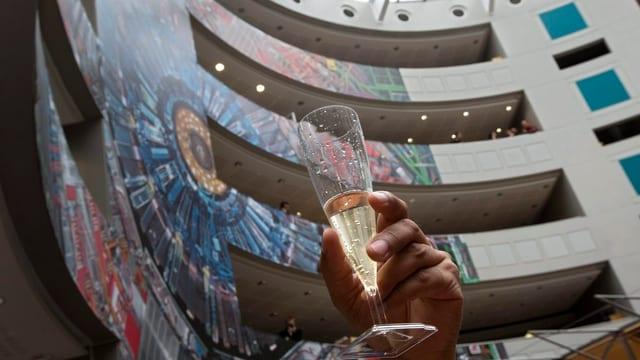 Eine Person hält ein Champagnerglas in die Höhe im Cern-Foyer.
