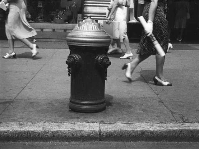 Auf einem schwarz-weissen Foto ist ein Hydrant auf einem Bürgersteig zu sehen.