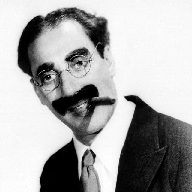 Groucho Marx posiert mit einer Zigarre im Mund.