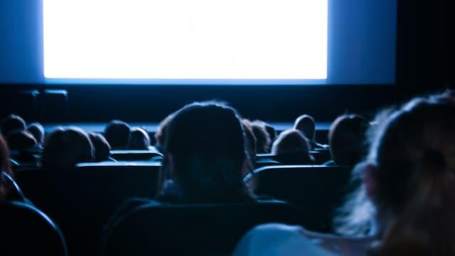 Kinobesucher sitzen in ihren Stühlen und warten auf den Beginn.