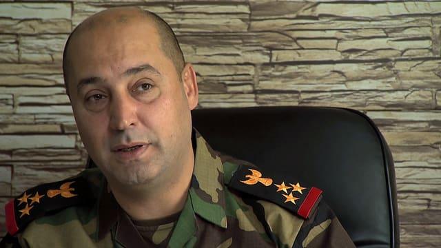 Der Drei-Sterne-General in Uniform an seinem Schreibtisch.