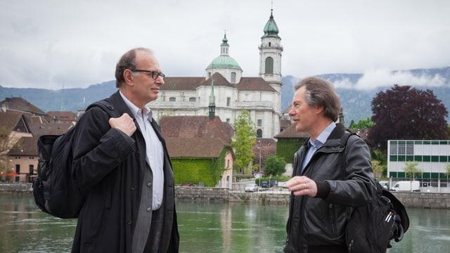 Hansueli Probst gestikuliert im Gespräch mit Felix Schneider. Im Hintergrund der Solothurner Dom und die Aare.