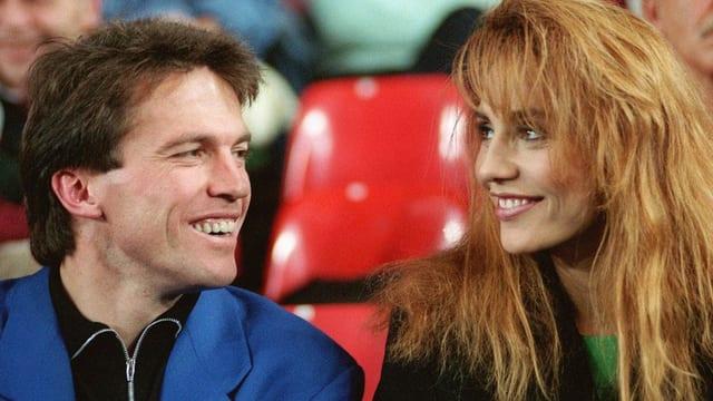 Lothar Matthäus im blauen Anzug blickt verliebt in die Augen von Lolita Morena, die eine braune Wuschelmäne mit Stirnfransen präsentiert.