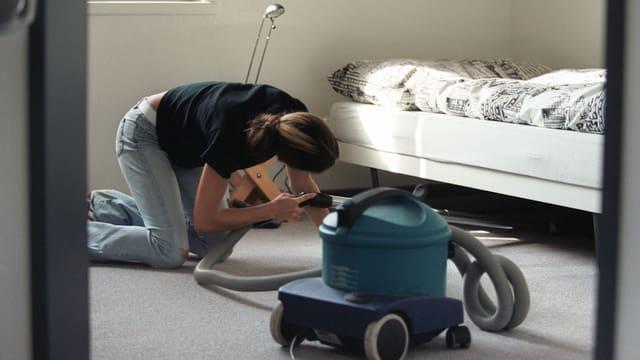 Eine Putzfrau saugt unter einem Bett