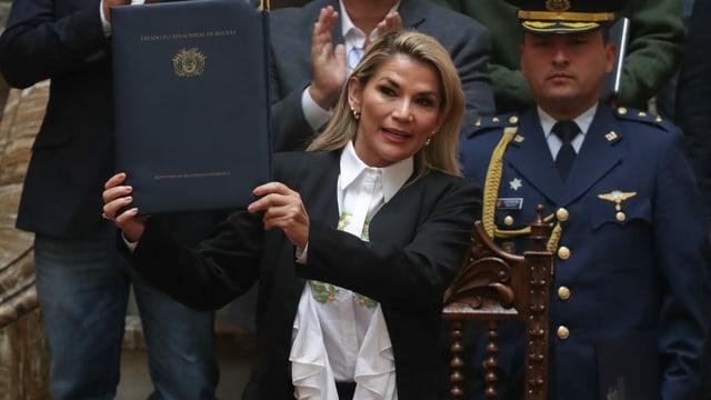 Jeanine Áñez zeigt ein Gesetz in die Kamera
