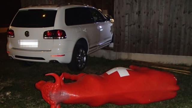 Eine rote Plastikkuh liegt am Boden - im Hintergrund steckt ein weisses Auto in einer Fassade aus Holz