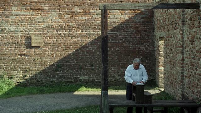 Claude Lanzmann steht unter einem Holzgebilde - dem Galgen von Theresienstadt. Im Hintergrund eine Mauer mit einer Gedenktafel.