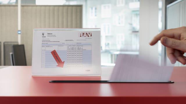 Eine Hand wirft das RAV-Anmeldeformular in eine Box.