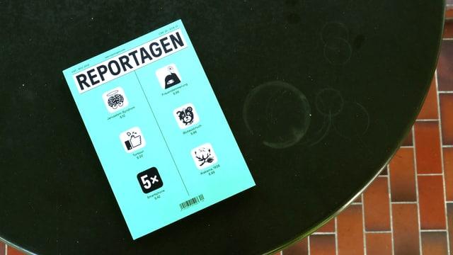 Ein Reportagen Heft liegt auf einem fleckigen Gartentisch.
