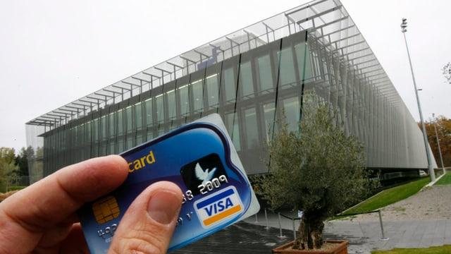 Jemand hält eine Visa-Kreditkarte vor dem Gebäude der Fifa in Zürich in die Höhe.