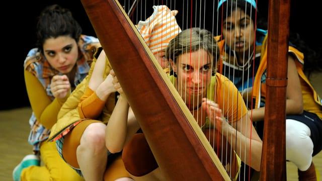 Junge Mädchen in bunten Kostümen verstecken sich hinter einer Harfe.
