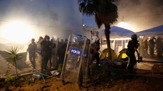 Polizisten im Tränengasnebel bei Nacht.