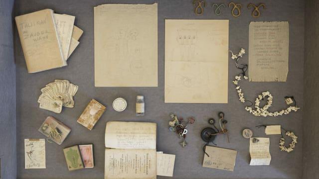 Mehrere Ausstellungsgegenstände: Ketten, Anhänger, Zeichnungen und Notizen.